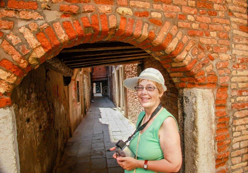 Szczęśliwa dojrzała turystyczna kobieta zostaje przeciw wąskiej ulicie w Wenecja obrazy stock