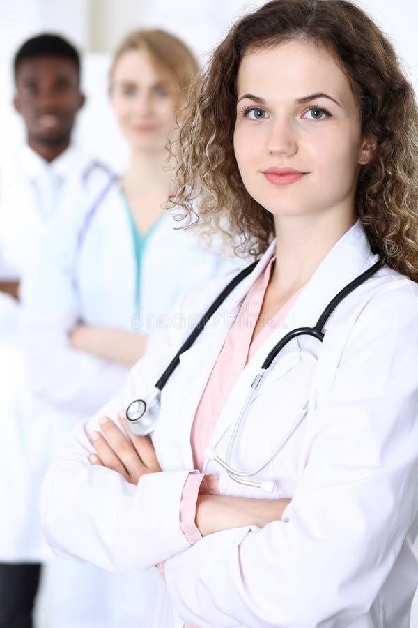 Szczęśliwa doktorska kobieta z medycznym personelem przy szpitalem Wielo- etniczni ludzie grup obraz royalty free