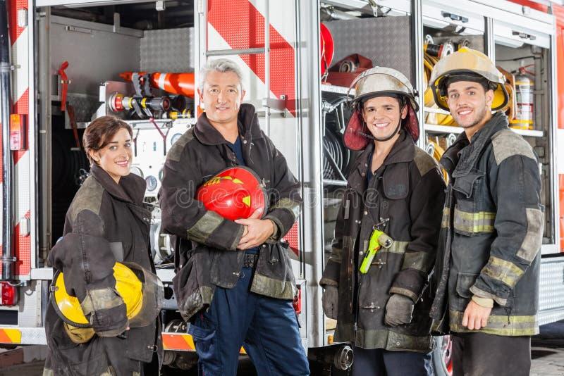 Szczęśliwa drużyna strażacy Przeciw ciężarówce zdjęcie royalty free
