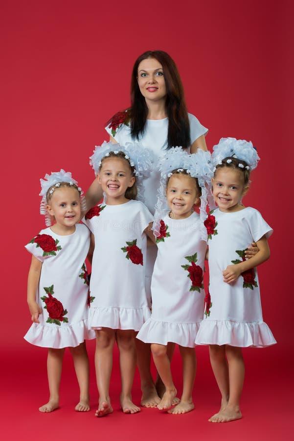 Szczęśliwa duża rodzina matka i cztery dziewczyny córki w upiększonych białych sukniach na prostym czerwonym tle w studiu obrazy stock