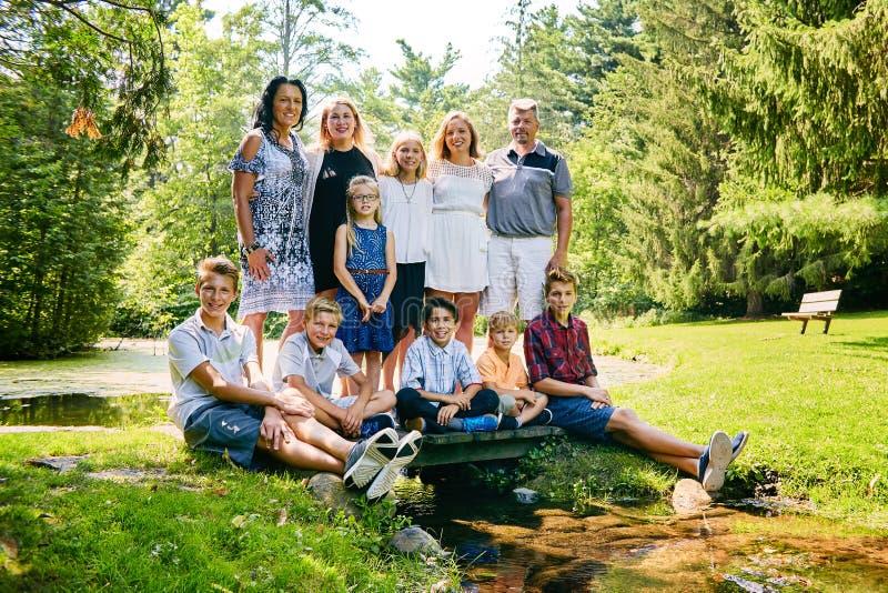 Szczęśliwa duża rodzina pozuje w scenicznym lato parku obrazy royalty free