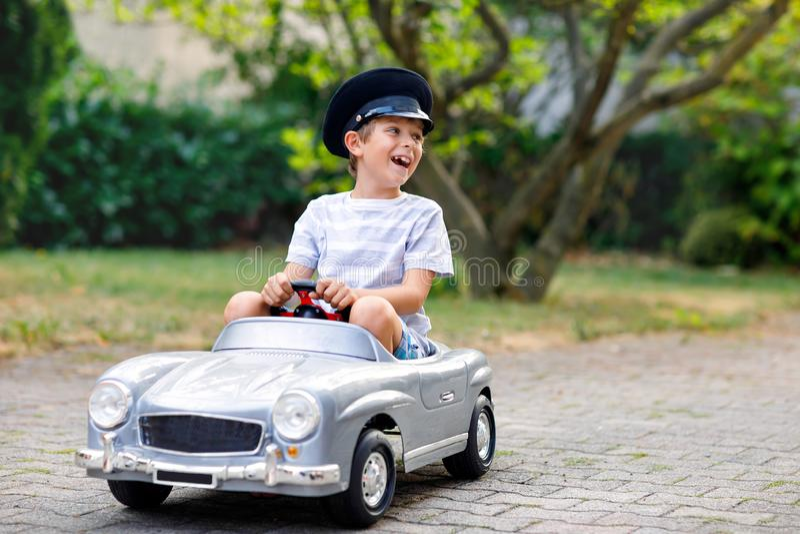 Szczęśliwa dzieciak chłopiec bawić się z dużym starym zabawkarskim samochodem w lato ogródzie, outdoors Zdrowy dziecko jedzie sta zdjęcia royalty free