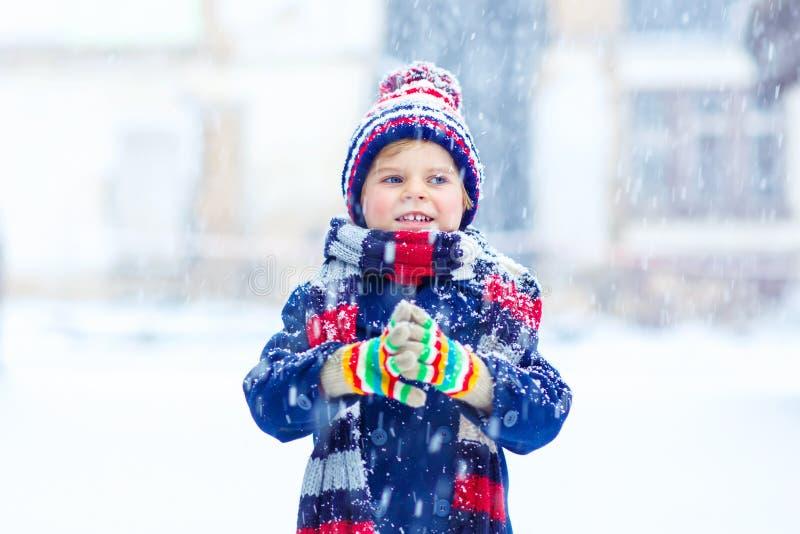 Szczęśliwa dzieciak chłopiec ma zabawę z śniegiem w zimie zdjęcia royalty free