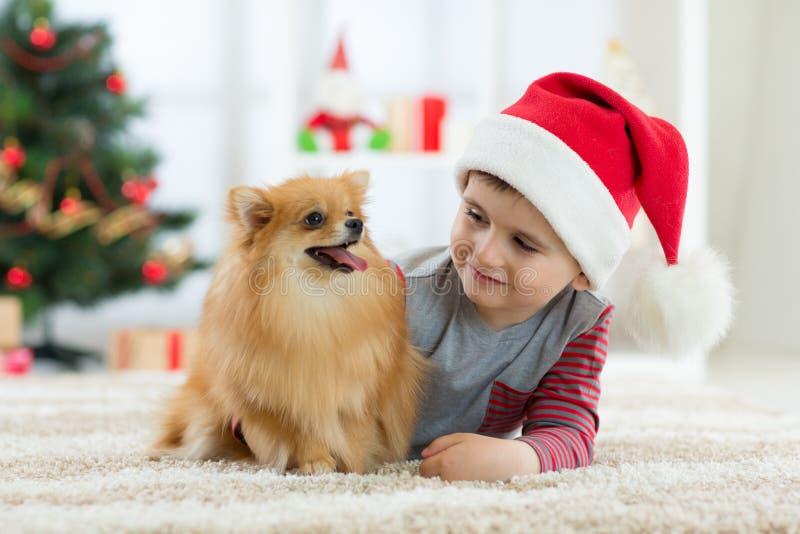 Szczęśliwa dzieciak chłopiec, pies jako ich prezent przy bożymi narodzeniami i Bożenarodzeniowy wnętrze zdjęcie royalty free
