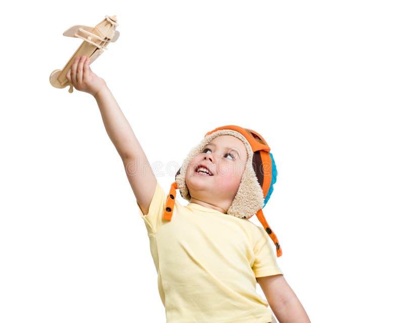 Szczęśliwa dzieciak chłopiec w hełma pilocie bawić się z drewnianym zabawkarskim samolotem pojedynczy białe tło zdjęcia royalty free