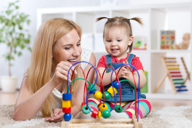Szczęśliwa dzieciak dziewczyna, mama bawić się zabawkę i obrazy stock