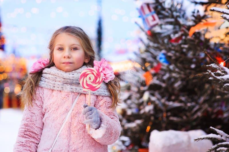 szczęśliwa dzieciak dziewczyna z boże narodzenie cukierkiem Zima wakacje portret w evening Moskwa mieście fotografia stock