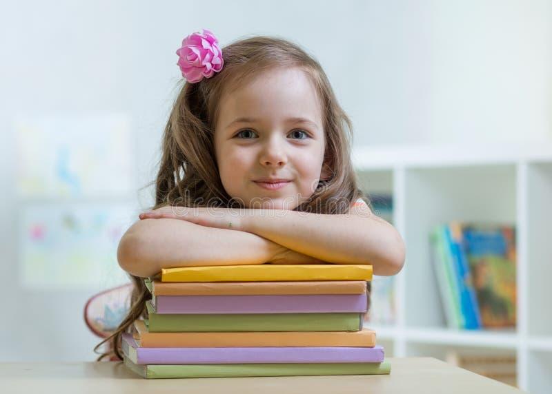 Szczęśliwa dzieciak dziewczyna z stertą książki w domu obraz stock