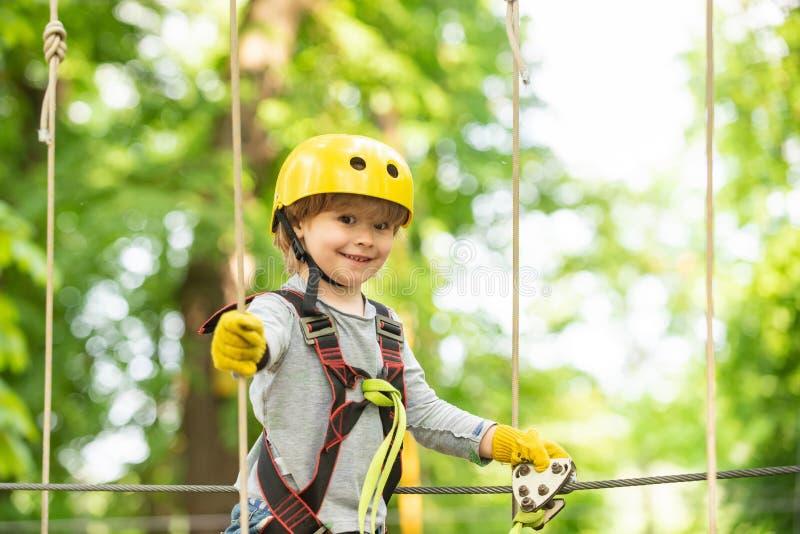 Szczęśliwa dziecko chłopiec dzwoni podczas gdy wspinający się wysokiego drzewa i arkan Portret piękny dzieciak na linowym parku w fotografia royalty free