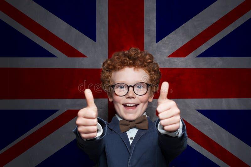 Szczęśliwa dziecko chłopiec pokazuje kciuk w górę UK chorągwianego tła przeciw Uczy się angielszczyzny swój chłodno zdjęcia stock
