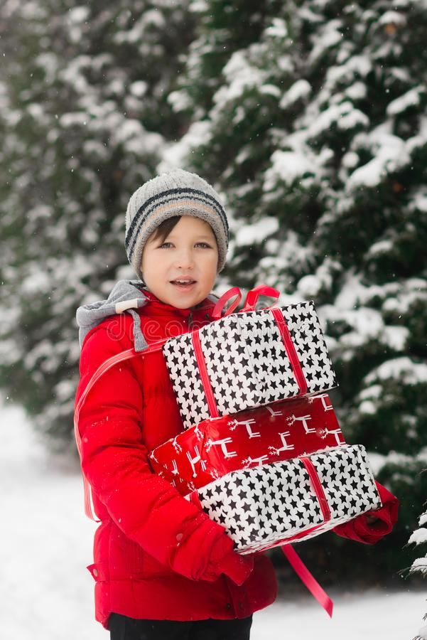 Szczęśliwa dziecko chłopiec trzyma kilka Bożenarodzeniowych prezenty w jego rękach obraz stock
