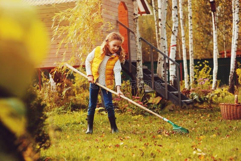 Szczęśliwa dziecko dziewczyna bawić się małej ogrodniczki w jesieni i podnosi opuszcza w kosz Sezonowa ogrodowa praca obraz royalty free
