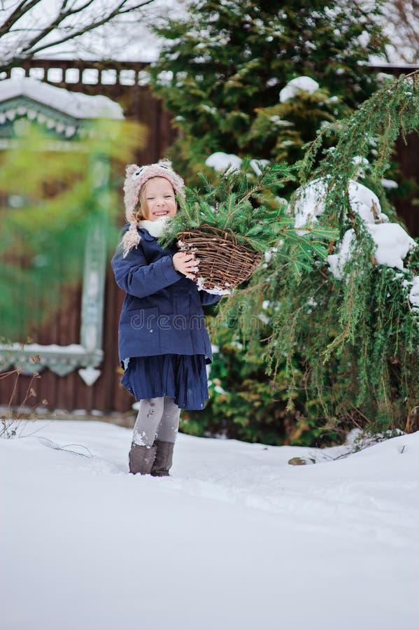 Szczęśliwa dziecko dziewczyna bawić się w zima śnieżnym ogródzie zdjęcia stock
