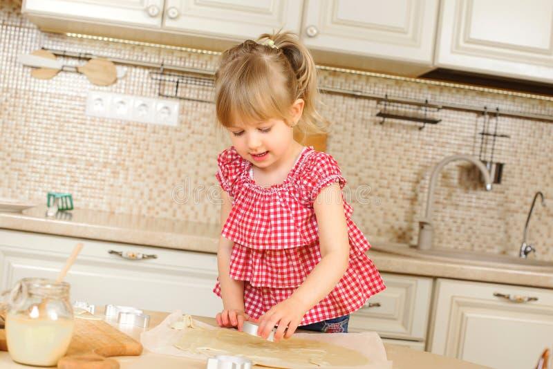Szczęśliwa dziecko dziewczyna gotuje na kuchni Dziecko córka piec ciastka szczęśliwego dzieciństwa Mały pomagier na kuchni urocza zdjęcie stock