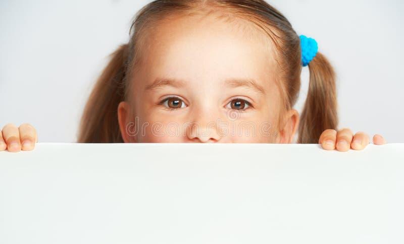 Szczęśliwa dziecko dziewczyna i pusty biały plakatowy billboard obraz stock