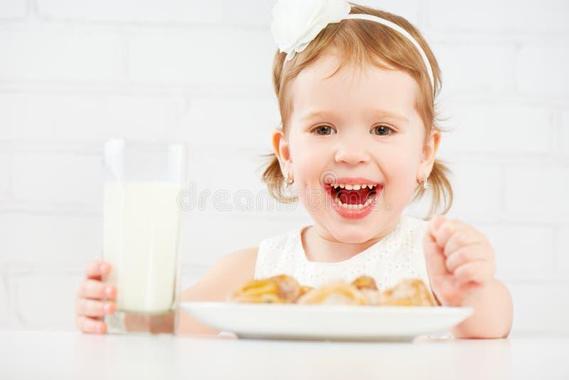 Szczęśliwa dziecko dziewczyna je ciastka i mleko zdjęcie stock