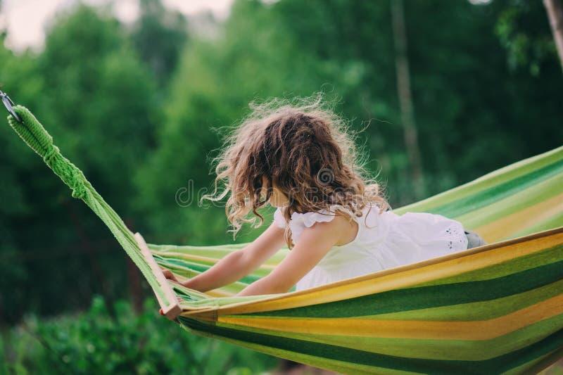Szczęśliwa dziecko dziewczyna relaksuje w hamaku na obozie letnim w lasowych Plenerowych sezonowych aktywność zdjęcia royalty free