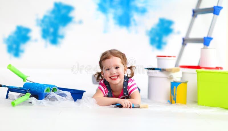 Szczęśliwa dziecko dziewczyna robi naprawom, farby ściana w domu obraz royalty free