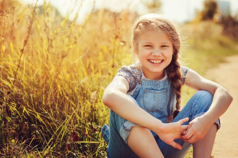 Szczęśliwa dziecko dziewczyna w cajgu kombinezonie bawić się na pogodnym polu, lato plenerowy styl życia fotografia stock