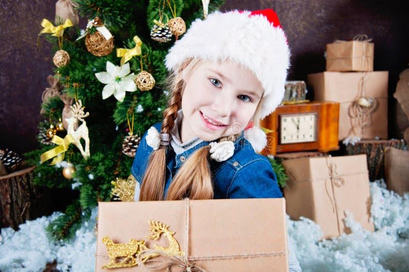 Szczęśliwa dziecko dziewczyna z Bożenarodzeniowymi prezentami blisko drzewa zdjęcia royalty free