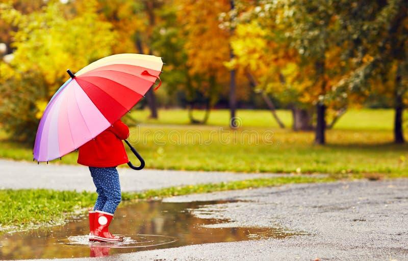 Szczęśliwa dziecko dziewczyna z parasolowym odprowadzeniem przez kałuż po autu zdjęcie royalty free