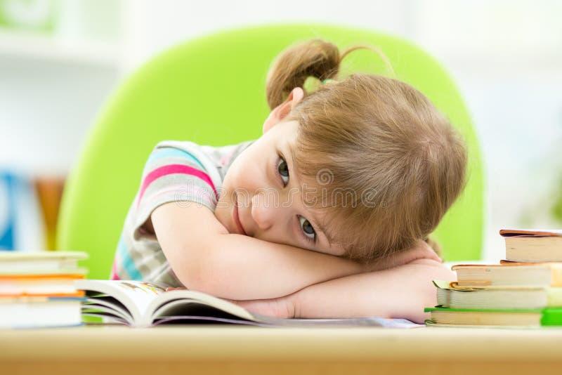 Szczęśliwa dziecko dziewczyna z stertą rezerwuje przy stołem obrazy stock