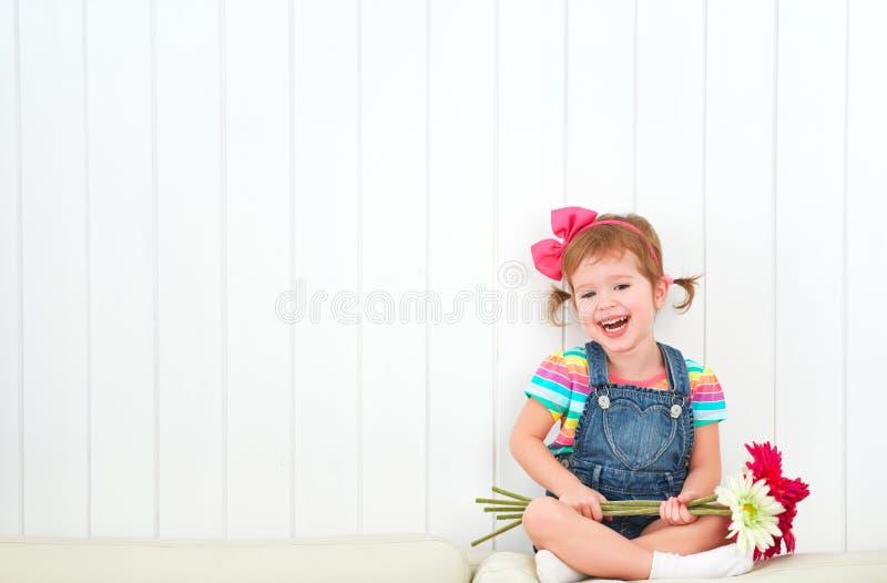 Szczęśliwa dziecko mała dziewczynka z bukietem gerbera kwitnie w empt fotografia stock