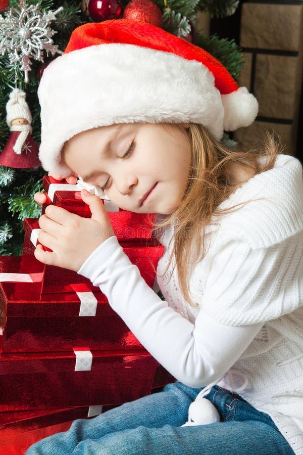 Szczęśliwa dziewczyna śpi blisko choinki w Santa kapeluszu z prezentami zdjęcie stock