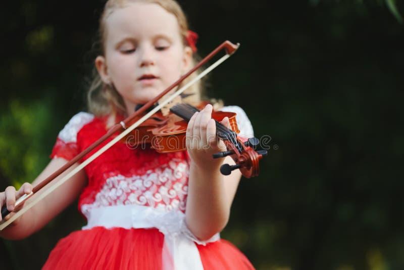 Szczęśliwa dziewczyna bawić się skrzypce w lato parku zdjęcie royalty free