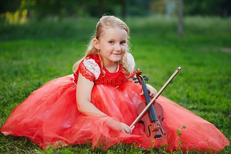 Szczęśliwa dziewczyna bawić się skrzypce w lato parku obrazy stock