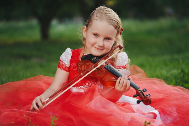 Szczęśliwa dziewczyna bawić się skrzypce w lato parku obraz royalty free