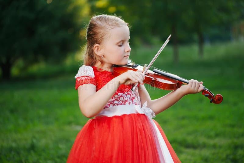Szczęśliwa dziewczyna bawić się skrzypce w lato parku obraz stock