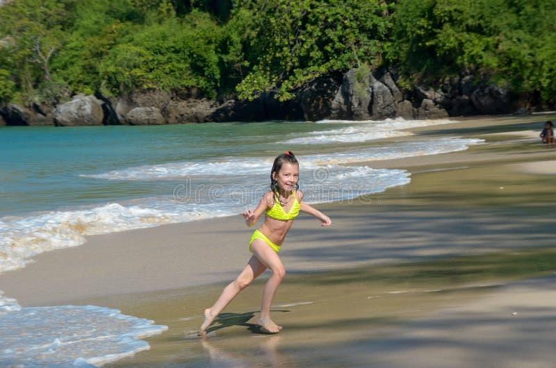 Szczęśliwa dziewczyna bawić się w morzu na tropikalnej plaży obrazy stock