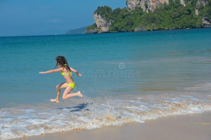 Szczęśliwa dziewczyna bawić się w morzu na tropikalnej plaży obrazy royalty free