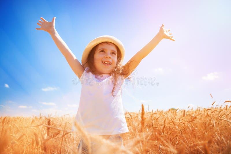 Szczęśliwa dziewczyna chodząca po złotej pszenicy, ciesząca się życiem na polu Piękno przyrody, niebieskie niebo i pole pszenicy  fotografia stock