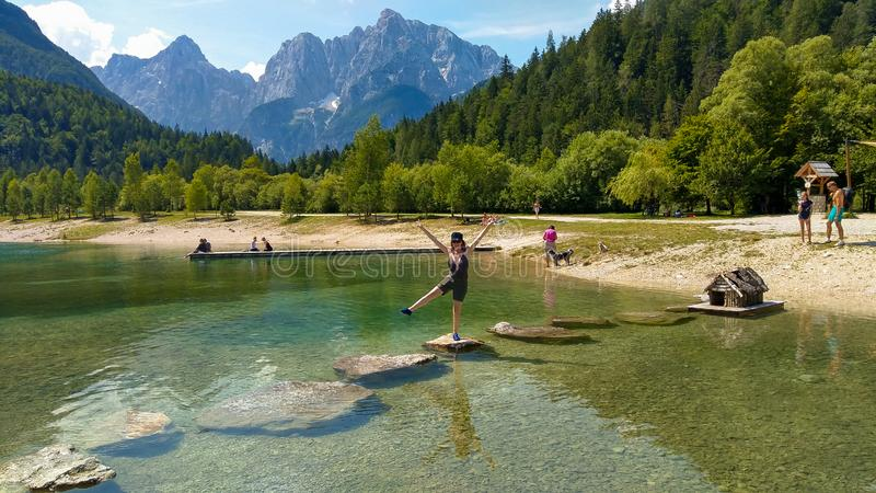 Szczęśliwa dziewczyna cieszy się wakacje na Jasna wysokogórskim jeziorze w Slovenia fotografia stock