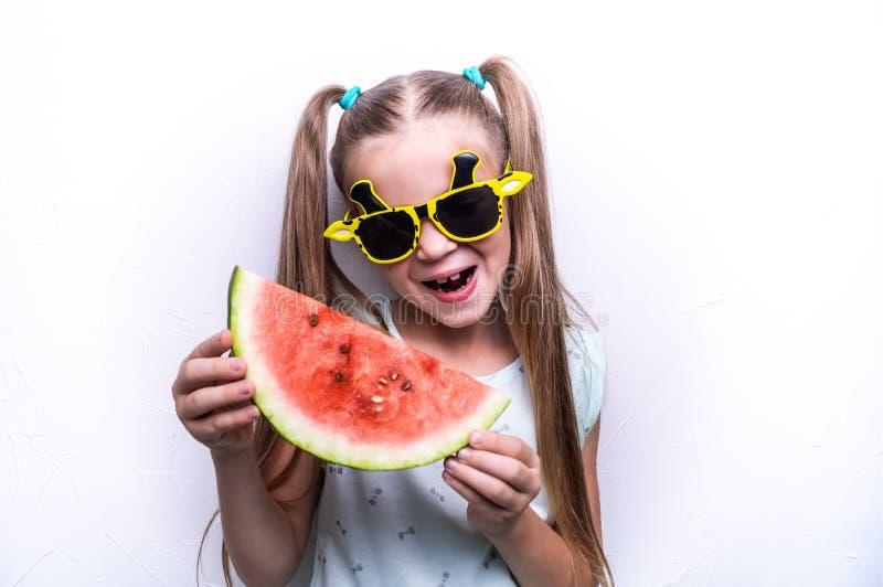 Szczęśliwa dziewczyna, dziecko w żółtych okularach przeciwsłonecznych, je dojrzałego czerwonego arbuza Portret obrazy royalty free
