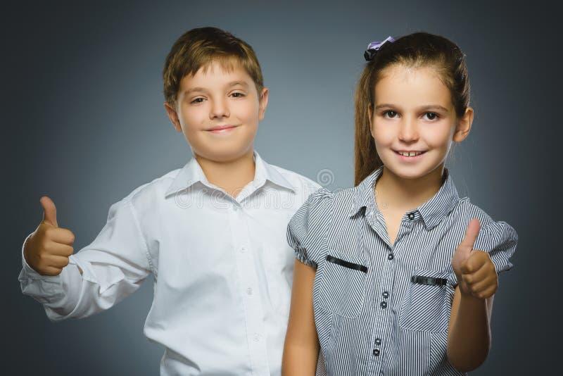 Szczęśliwa dziewczyna i chłopiec pokazuje thubs up Portretów dzieci ono uśmiecha się odizolowywam na popielatym obraz stock