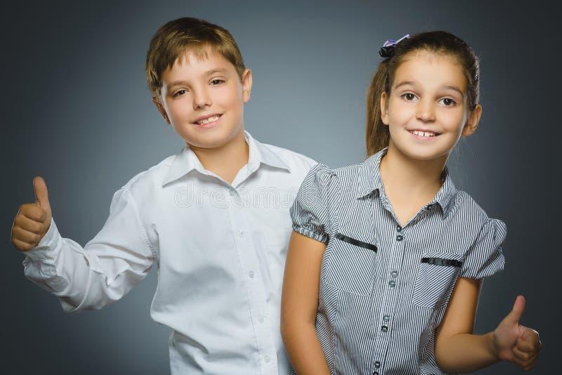 Szczęśliwa dziewczyna i chłopiec pokazuje thubs up Portretów dzieci ono uśmiecha się odizolowywam na popielatym zdjęcie royalty free