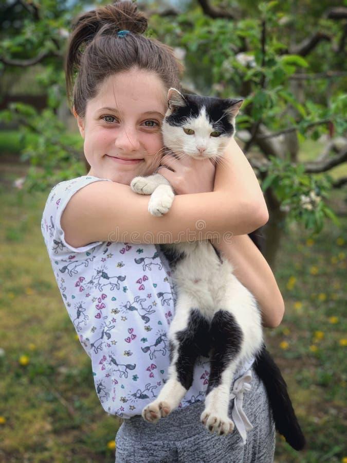 Szczęśliwa dziewczyna i jej czarny i biały barwiony kot obrazy stock