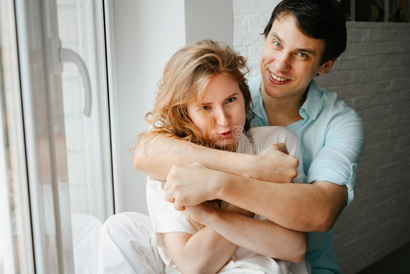Szczęśliwa dziewczyna i mężczyzna ściska blisko okno w domu zdjęcia stock