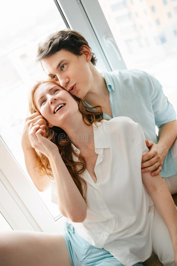 Szczęśliwa dziewczyna i mężczyzna ściska blisko okno w domu zdjęcia royalty free