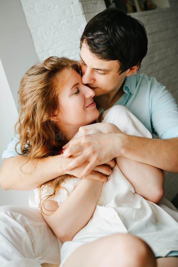 Szczęśliwa dziewczyna i mężczyzna ściska blisko okno w domu fotografia stock