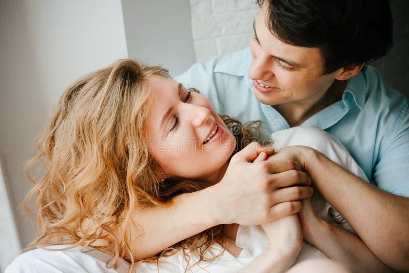 Szczęśliwa dziewczyna i mężczyzna ściska blisko okno w domu obraz stock