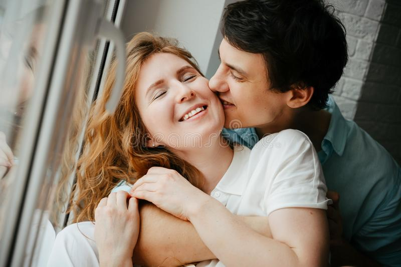 Szczęśliwa dziewczyna i mężczyzna całuje blisko okno w domu fotografia stock