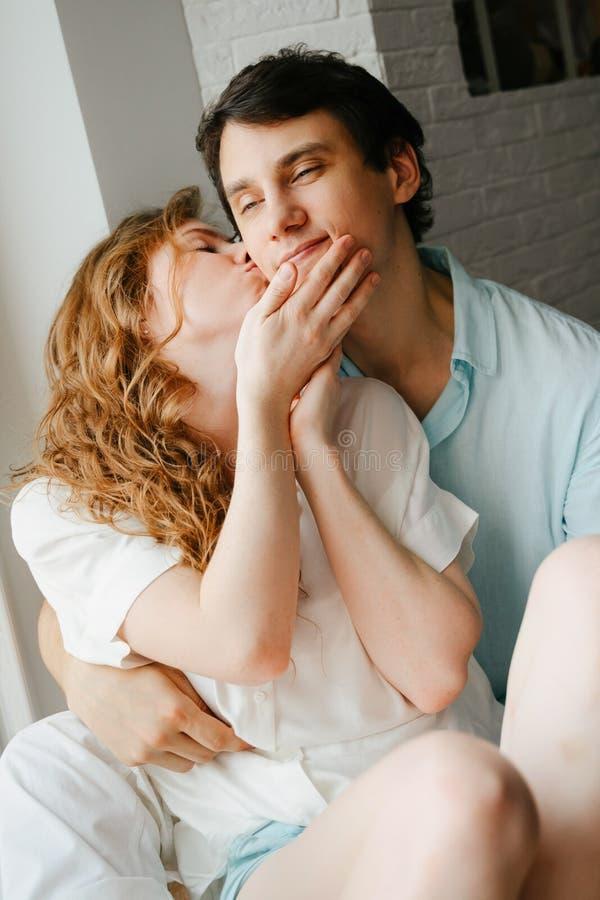 Szczęśliwa dziewczyna i mężczyzna całuje blisko okno w domu zdjęcia royalty free