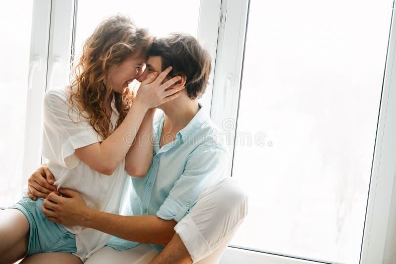 Szczęśliwa dziewczyna i mężczyzna całuje blisko okno w domu obraz stock