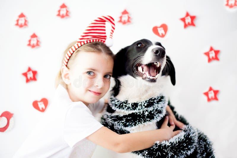 Szczęśliwa dziewczyna i pies przy bożymi narodzeniami zdjęcie stock