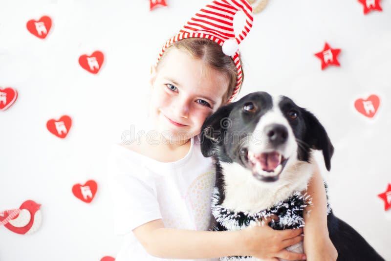 Szczęśliwa dziewczyna i pies przy bożymi narodzeniami fotografia royalty free