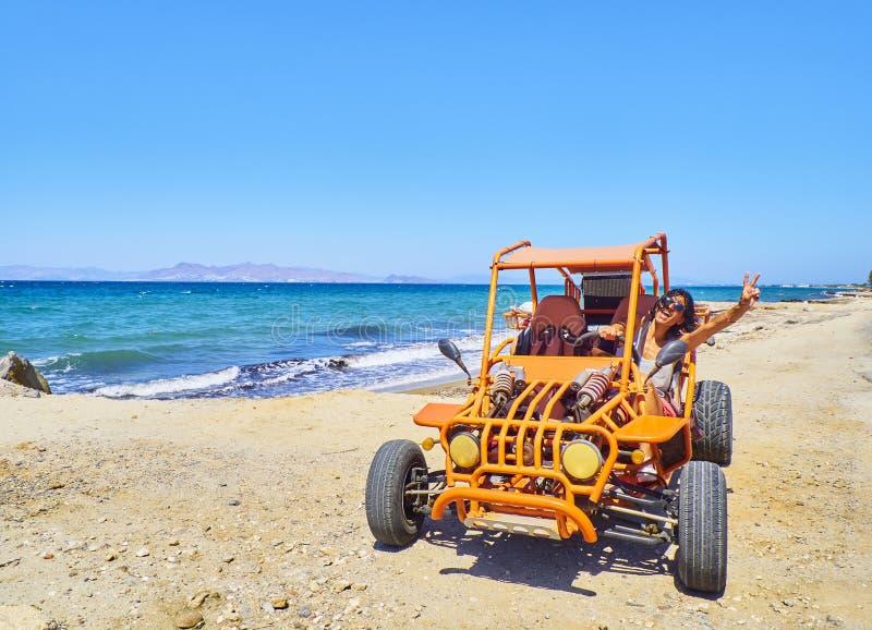 Szczęśliwa dziewczyna jedzie powozika na plażowej diunie plaża przewodniczy Greece wyspy kefalos kos pomarańcze parasole południe zdjęcie royalty free